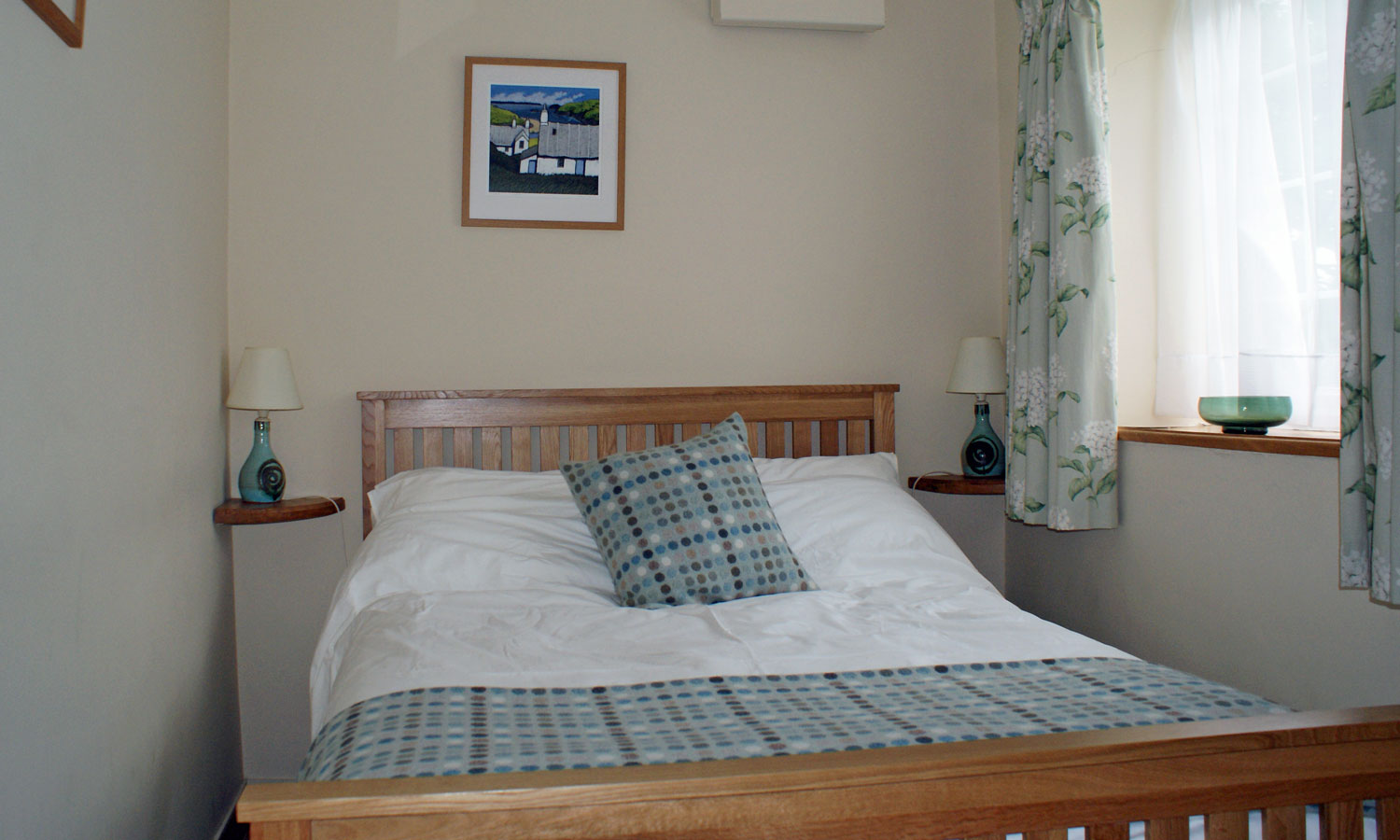 Double bed in Eynons Holiday Cottage with local Melyn Ty Gwynt throw and pillow