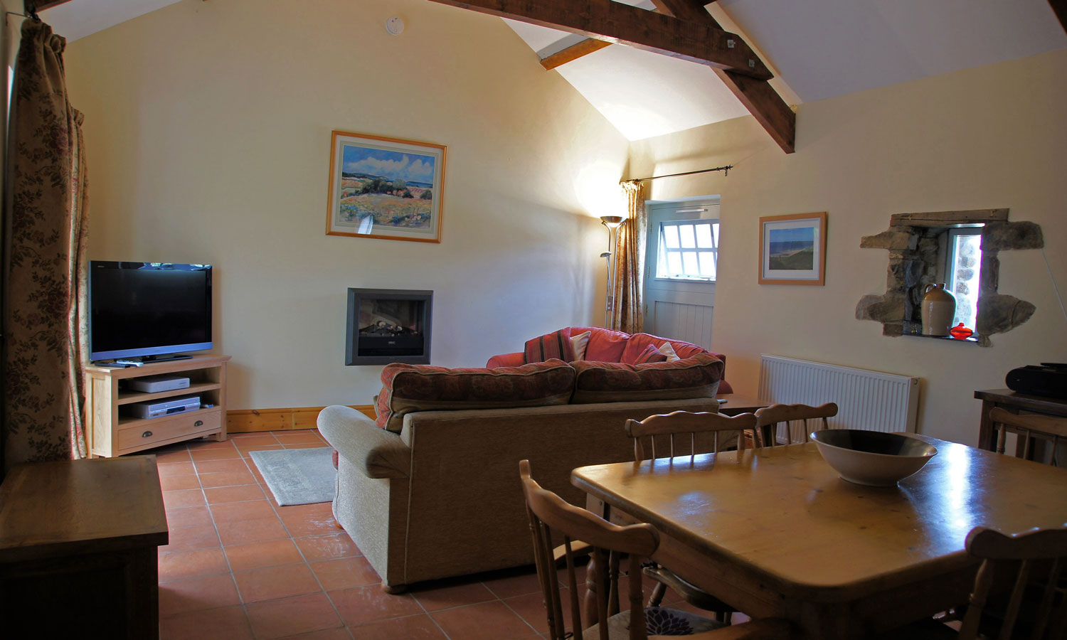 Comfortable sitting room of Meadow Barn Holiday Cottage, Pembrokeshire. Pictures of Newgale Beach, Pembrokeshire