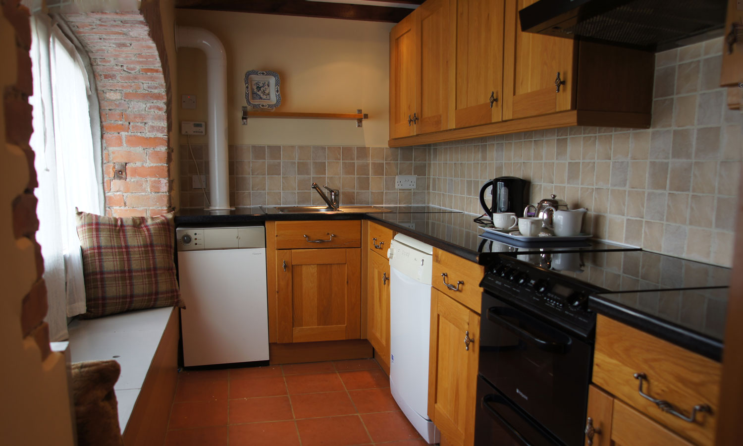 Modern and well equipped kitchen in Meadow Barn Holiday Cottage. Natural colours and textures reflect local beaches